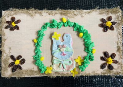 Na zdjęciu nagrodzona praca konkursowa na wielkanocny mazurek na którym znajduje się zajączek otoczony zielonym wiankiem i kwiatkami z rodzynek.