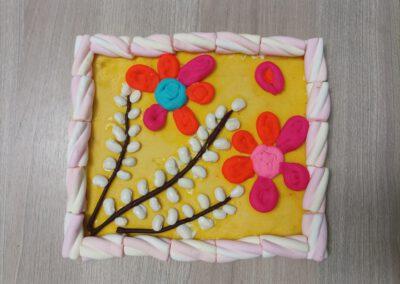 Na zdjęciu mazurek wielkanocny wykonany z pianek marshmallow oraz ozdobiony baziami i kwiatami z ciastoliny.