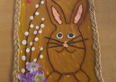 Na zdjęciu wyróżniona praca konkursowa na mazurek wielkanocny. Praca przedstawia zajączka otoczonego baziami i kwiatami.