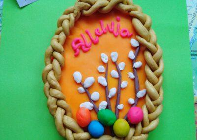 Na zdjęciu wykonany z plasteliny mazurek z kolorowymi jajeczkami, baziami i napisem Alleluja. Praca wykonana na konkurs plastyczny.