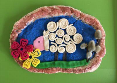 Zdjęcie przedstawia pracę konkursową na mazurek wielkanocny, na którym znajduje się baranek wąchający kolorowe kwiaty.