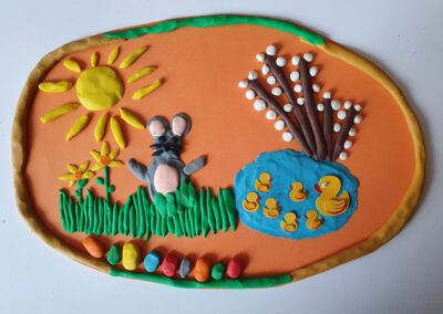 Zdjęcie przedstawia pracę plastyczną przedstawiającą zajączka z plasteliny wśród zielonej trawy oraz staw z kaczkami nad którym rosną bazie.