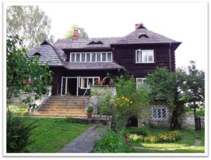 Drewniany dom w otoczeniu zieleni, w którym mieści się Muzeum Marii Kuncewiczowej